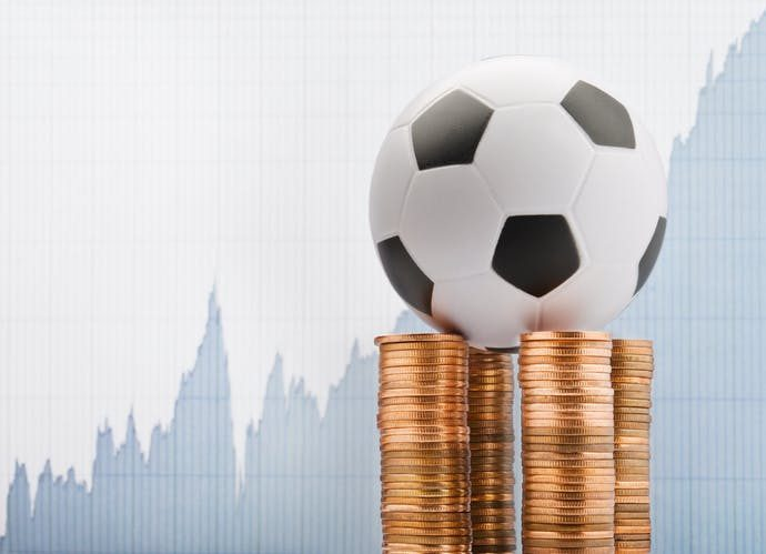 A football balanced on a pile of coins against a financial report backdrop.