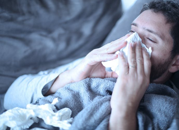 A man suffering a breakthrough infection, blowing his nose