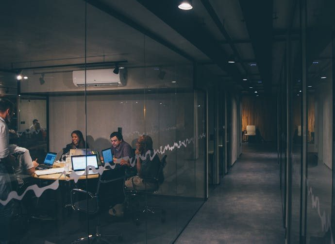 A group of work colleagues sitting in a late night meeting in a dark office.
